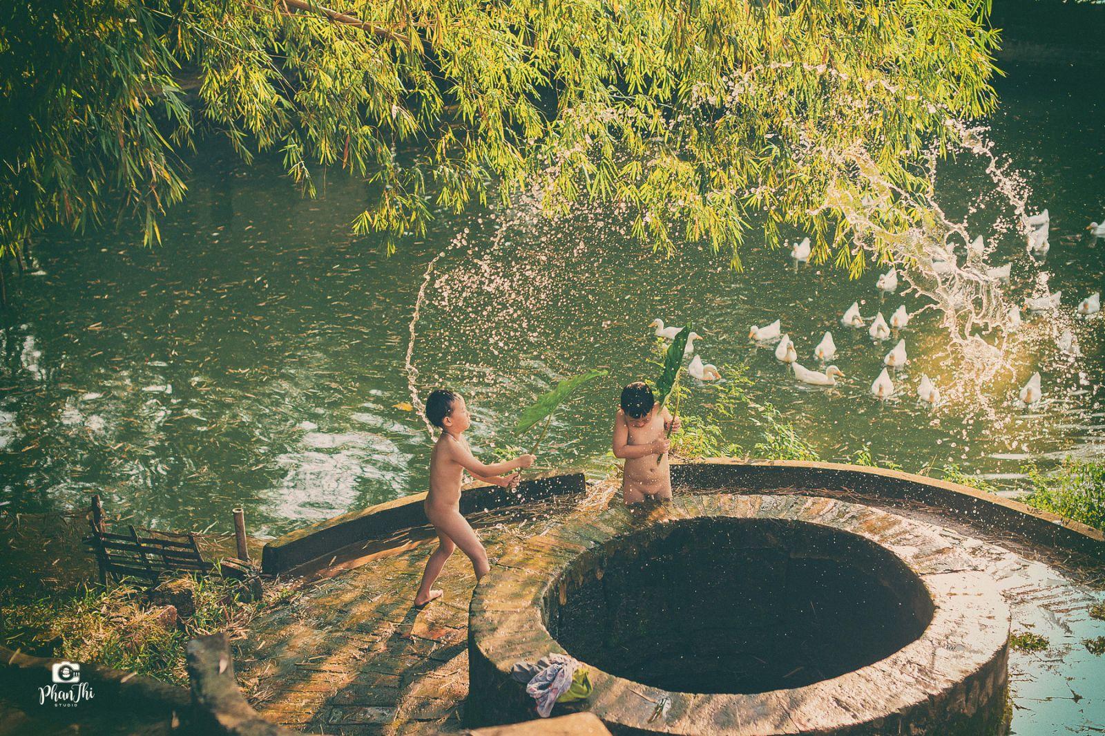Hình ảnh quê hương những đứa trẻ tắm mát bên giếng