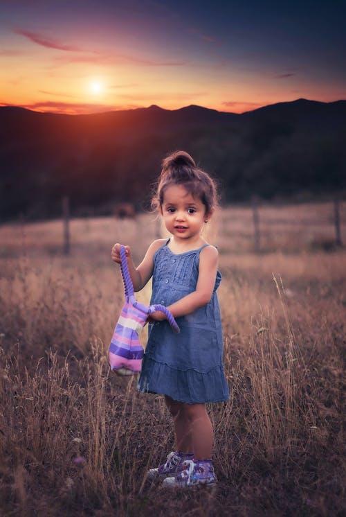 Cô bé con mặc váy xinh đứng giữa đồng cỏ