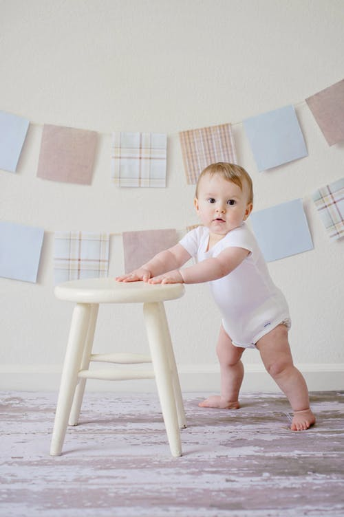 Em bé đáng yêu đang bắt đầu tập đi