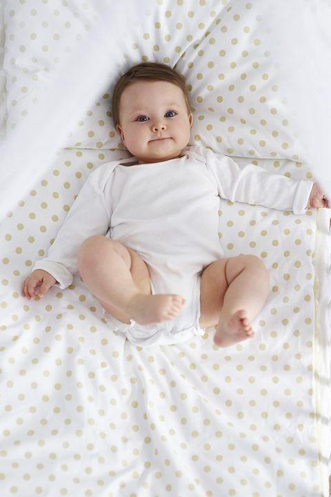 Em bé đáng yêu nằm co chân