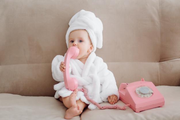 Em bé quấn khăn tắm trắng và ngậm điện thoại hồng