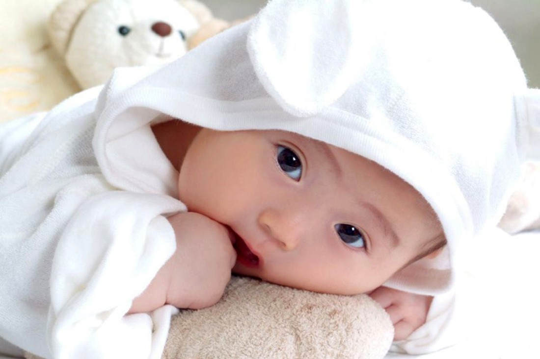 Em bé xinh xắn mặc đồ trắng