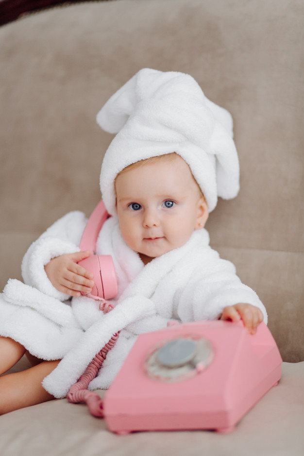 Em bé xinh xắn quấn khăn tắm nghe điện thoại